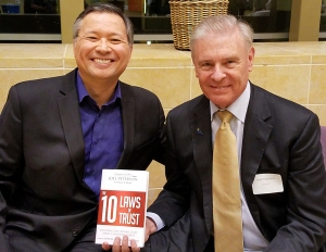 "Joel Peterson holds his book ""The 10 Laws of Trust ""-- and Tom Marcoux celebrates Joel's wisdom"